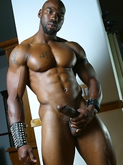 Bald ebony guy shows his stong muscles